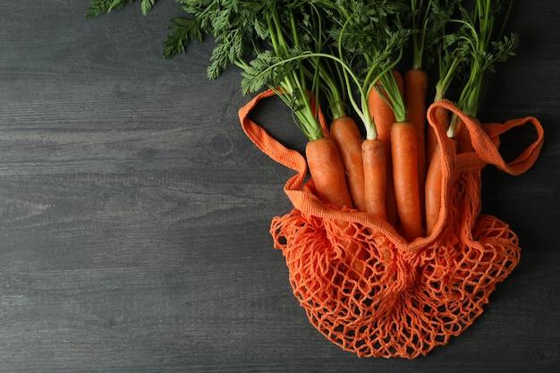 Borsa di stringa con carota su una superficie di legno scuro