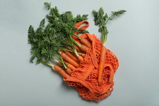 Borsa in corda con carota su superficie grigio chiaro