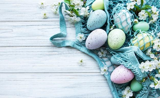 Borsa in corda con uova di pasqua e fiori primaverili in un angolo di un tavolo in legno rustico