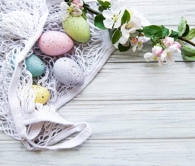 Borsa in corda con uova di pasqua e fiori primaverili