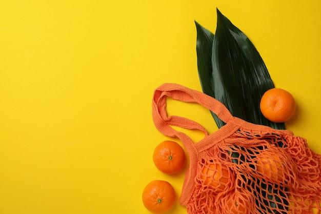 Borsa di stringa con mandarini e foglie su giallo
