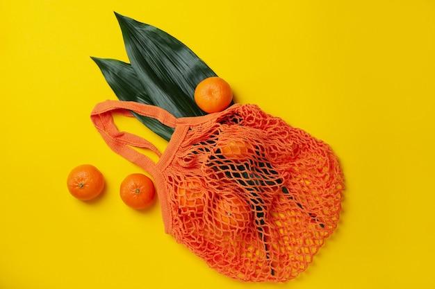 Borsa in corda con mandarini e foglie