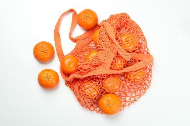 Borsa a tracolla con mandarini su sfondo bianco