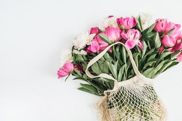 String bag con fiori di peonia rosa e bianchi su superficie bianca