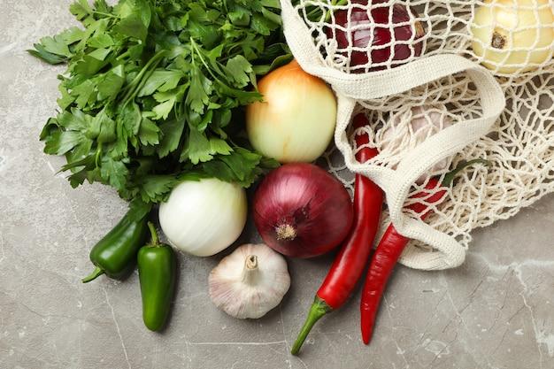 Borsa di corda con verdure piccanti e prezzemolo su sfondo grigio strutturato