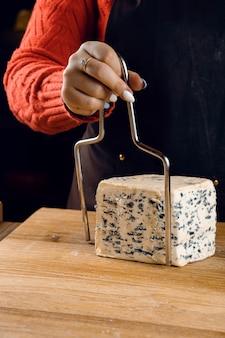 Stringa per affettare il formaggio blu. misto di formaggi sulla piastra. affettare dorblu, gorgonzola, roquefort. cucina gourmet francese.