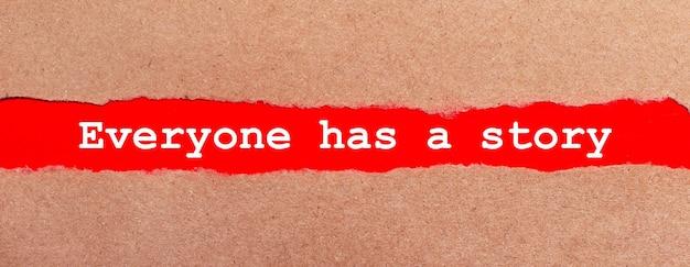 Una striscia di carta rossa sotto la carta marrone strappata. caratteri bianchi su carta rossa tutti hanno una storia. vista dall'alto