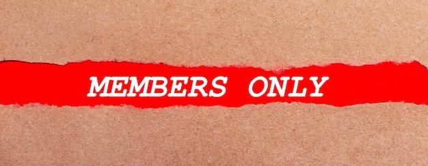 Una striscia di carta rossa sotto la carta marrone strappata. lettere bianche su carta rossa solo per i soci. vista dall'alto