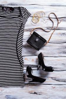 Abito nero a righe e tacchi. borsa scura con bracciali chiari. abito da sera casual da donna. ultima merce venduta a prezzo scontato.