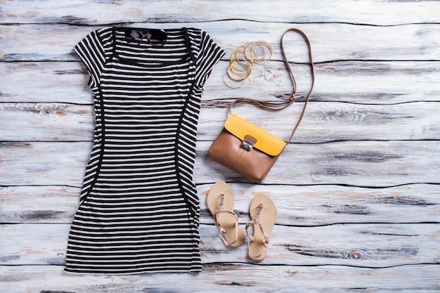 Abito nero a righe e sandali. sandali beige con abito scuro. vestito estivo casual per ragazze. abbigliamento di alta qualità in stock.