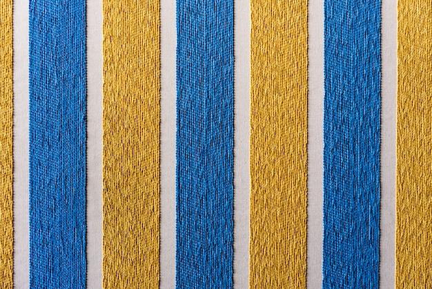 Colori a strisce blu e gialli con trama ruvida del tessuto, sfondo colorato.