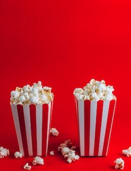 Scatola a strisce con popcorn su sfondo rosso