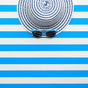 Cappello a righe e occhiali da sole su sfondo bianco-blu. vista dall'alto, piatto.