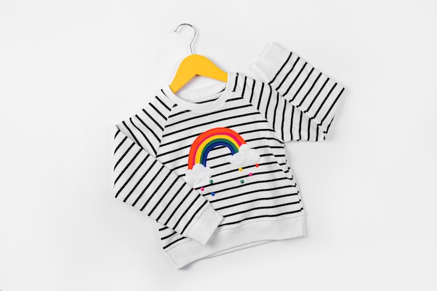 Maglione a righe con arcobaleno sul gancio su sfondo bianco. vestito carino per bambini. abbigliamento per bambini per l'autunno o la primavera.
