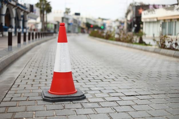 Coni arancioni a strisce sulla strada asfaltata
