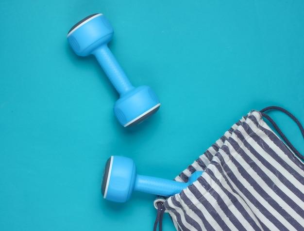 Borsa sportiva a strisce con manubri su sfondo blu. sport ancora in vita. vista dall'alto.