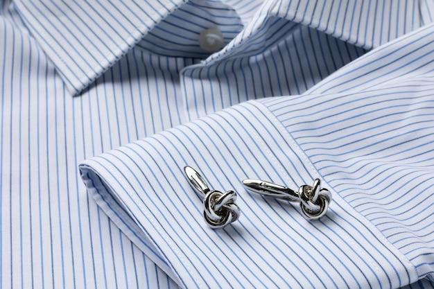 Camicia da uomo a righe bianche e blu da vicino con gemelli a forma di nodo. avvicinamento. messa a fuoco selecrive.