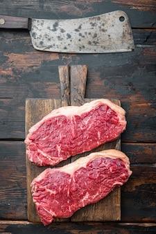 Bistecca di controfiletto, carne di manzo cruda tagliata, sul vecchio tavolo di legno wooden