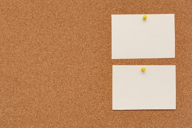 Carte per appunti spogliate con puntine da disegno sulla bacheca di sughero