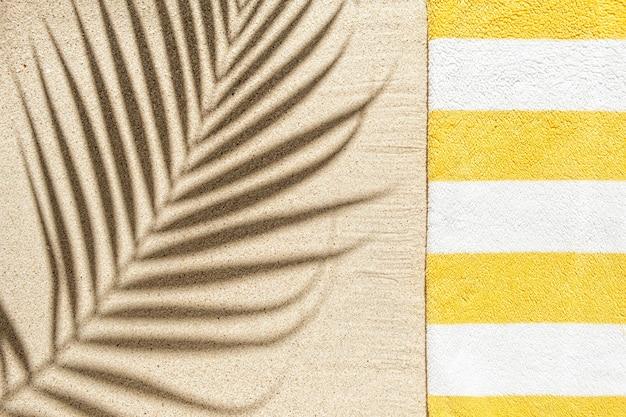 Asciugamano da spiaggia giallo e bianco a righe e ombra di foglie di palma su sfondo di spiaggia sabbiosa, vista dall'alto