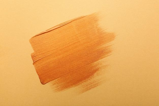 Tratti di vernice dorata su sfondo arancione