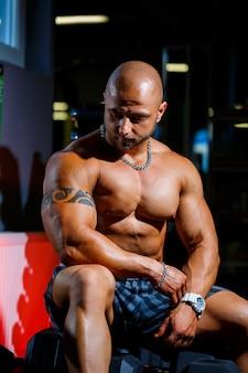 Forte, adulto, in forma, allenatore maschio muscoloso in posa per un servizio fotografico in palestra in abbigliamento sportivo, mostrando i suoi muscoli