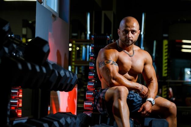 Forte, adulto, in forma, muscoloso allenatore maschio in posa per un servizio fotografico in palestra in abbigliamento sportivo, mostrando i suoi muscoli