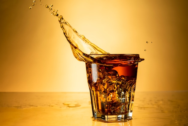 Alcol forte in un bicchiere con splash su uno sfondo di sfondo giallo con la riflessione