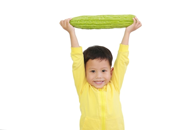 Il forte bambino asiatico ha sollevato la zucca amara sopra la sua testa isolata su fondo bianco con il percorso di ritaglio