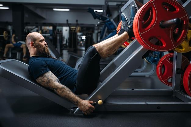 Forte atleta sulla macchina ginnica con bilanciere, allenamento in palestra.