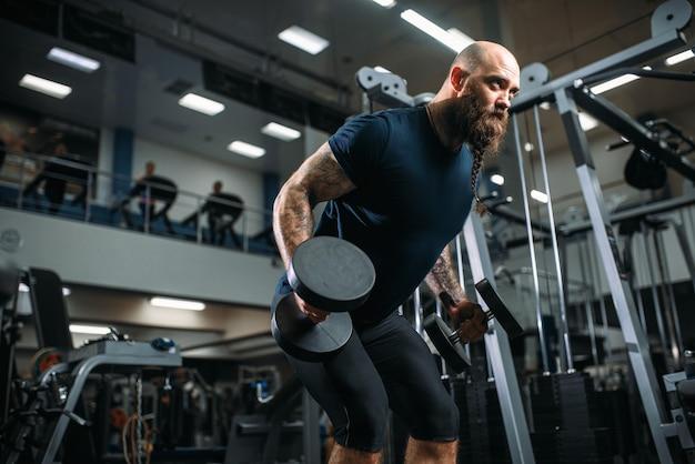 Forte atleta con manubri, allenamento in palestra