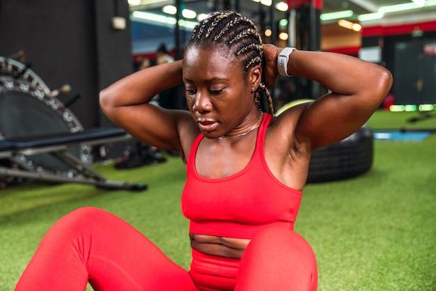 Forte donna di colore atletica in una palestra che fa esercizi addominali in abiti sportivi rossi