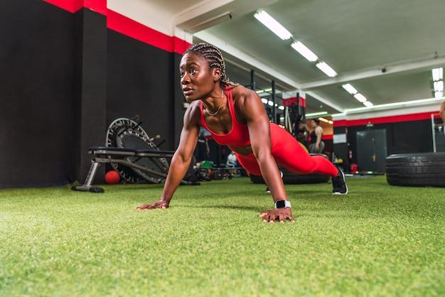 Forte donna nera atletica in una palestra che fa esercizi di flessione in abiti sportivi rossi