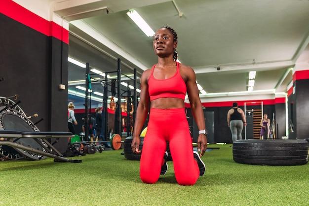 Forte donna di colore atletica in una palestra, pronta e concentrata sulle ginocchia per fare sport, vestita con abiti sportivi rossi red