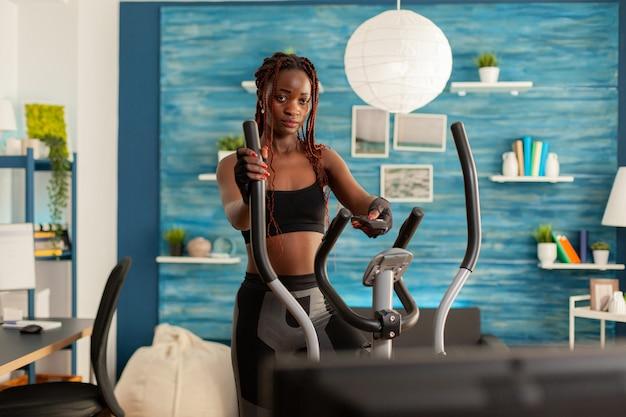 Forte donna nera in forma atletica che fa allenamento incrociato che si esercita nel soggiorno di casa usando l'e...