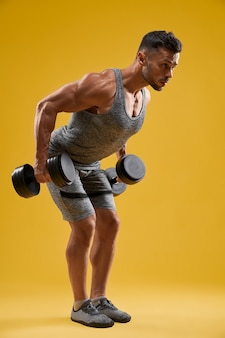 Forte uomo atletico che fa esercizio con i manubri