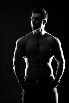 Forte modello di fitness uomo atletico. maschio che mostra addominali scolpiti. isolato su sfondo scuro. foto in bianco e nero.