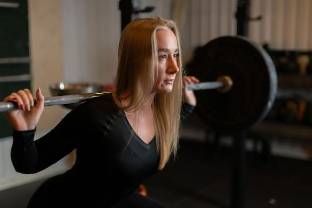 Una donna forte e atletica con i capelli biondi esegue un esercizio di squat con un bilanciere sulla schiena e guarda avanti in palestra.