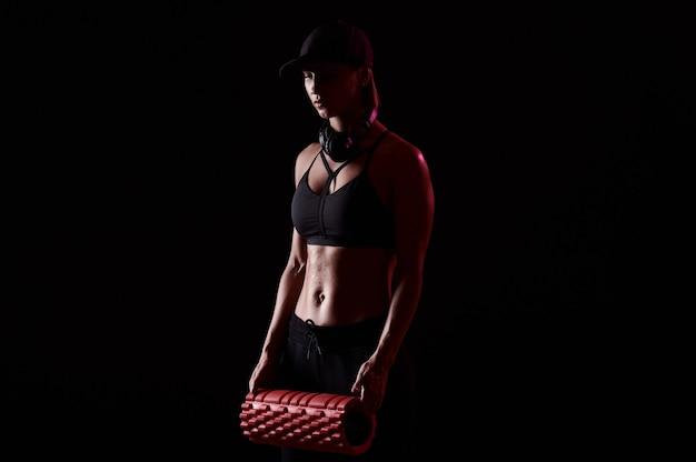 Forte donna atletica con rullo massaggiante e cuffie su sfondo nero isolato