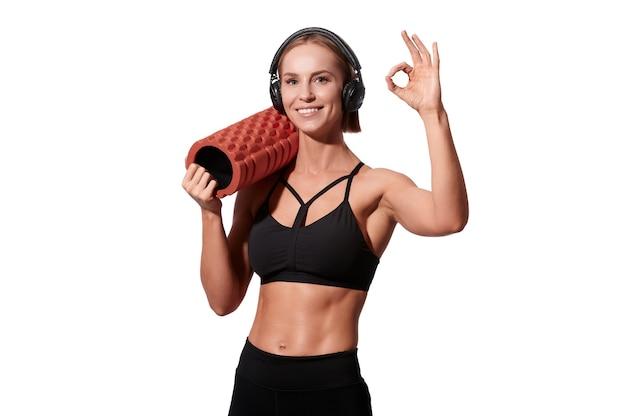 La forte donna atletica con il rullo di massaggio e le cuffie mostra il gesto giusto su fondo isolato bianco