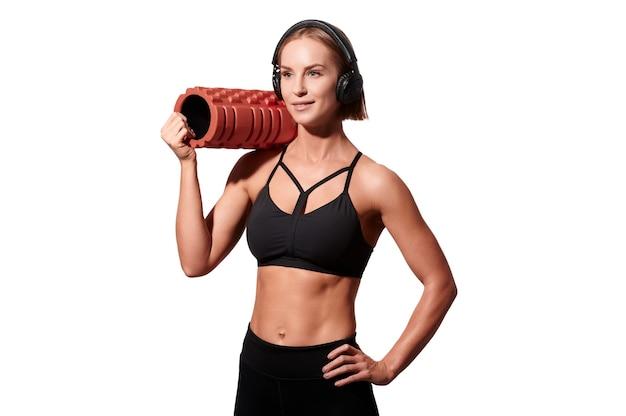 Forte donna atletica con rullo massaggiante e cuffie su sfondo bianco isolato