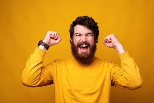 Il forte uomo barbuto sta facendo il gesto del vincitore con entrambe le mani su sfondo giallo.
