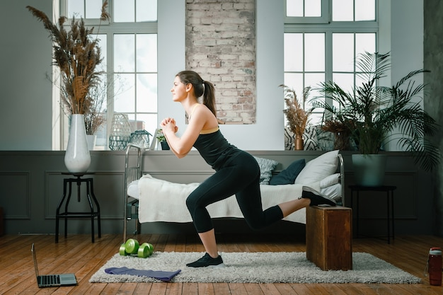 Una ragazza di fitness sportiva forte e bella in abiti sportivi si lancia con le scatole