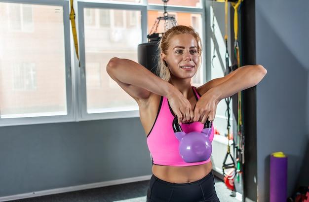 Forte donna bionda che si esercita con un peso di kettlebell. allenamento con i pesi liberi