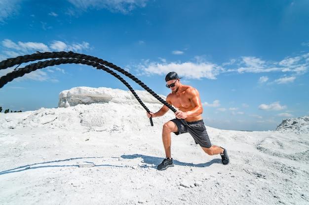 Forte bodybuilder in un berretto e occhiali da sole che si allenano con le corde all'aperto