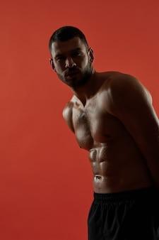 Forte atleta caucasico isolato su sfondo rosso