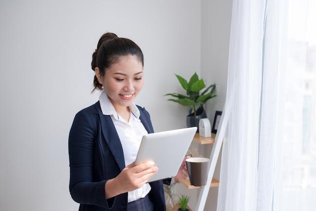 Forte, sicura di sé, donna d'affari asiatica in piedi nel corridoio di un edificio per uffici, con in mano un tablet