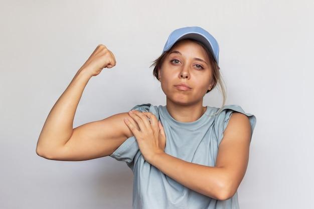 Una giovane donna bionda caucasica forte e sicura con una maglietta grigia e un berretto alza il braccio e mostra il bicipite