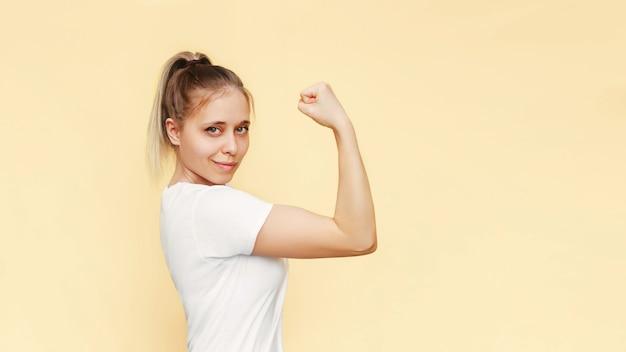 La giovane donna bionda caucasica forte e sicura alza il braccio e mostra il bicipite su sfondo giallo