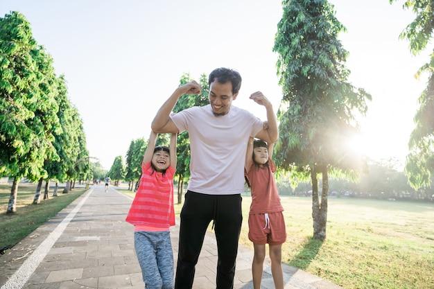 Papà forte con i bambini appesi al braccio mentre si allena